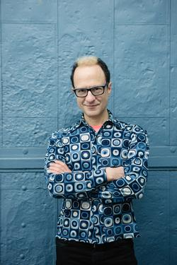 A photograph of poet Wayne Koestenbaum, wearing a blue printed shirt, with arms crossed in front of a blue wall.