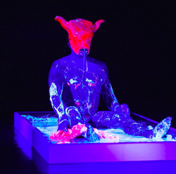 Ron Athey, Acephalous Monster, 2019, MoCA Skopje. Photo: Andreja Kargačin. [The artist Ron Athey, wearing a minotaur mask, is seated in a shallow box of viscous fluids under a blacklight in shades of blue, white, and pink, covered in drippy fluids.]