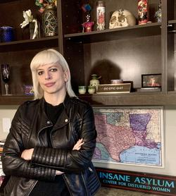 This is a photo of Security Studies Professor, Natalie Baker wearing a leather jacket, arms folded and leaning against wall shelves.