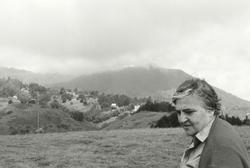 A black and white photo of poet and painter Etel Adnan in a hillside meadow beneath clouds.
