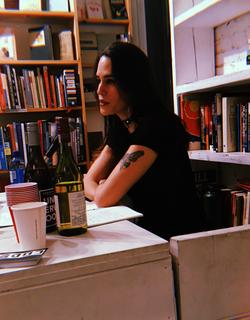 A photograph of poet Kay Gabriel sitting an a desk, near bookshelves, an open notebook, wine bottles and cups.