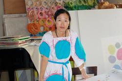 This is a photo of Korean Artist, Minjung Kim at her studio with many colors, including her dress with large, turquoise circles.