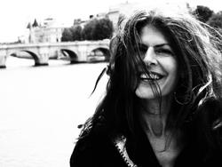 A black and white photo of poet Eleni Sikelianos smiling at Pont des Arts.