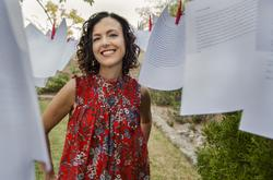 A photo of poet Rosa Alcalá in a red shirt, smiling between sheets of paper hung on a clothesline.