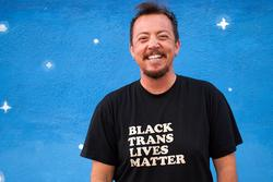 A photo of poet TC Tolbert, wearing a Black Trans Lives Matter shirt in front of a background of painted stars.